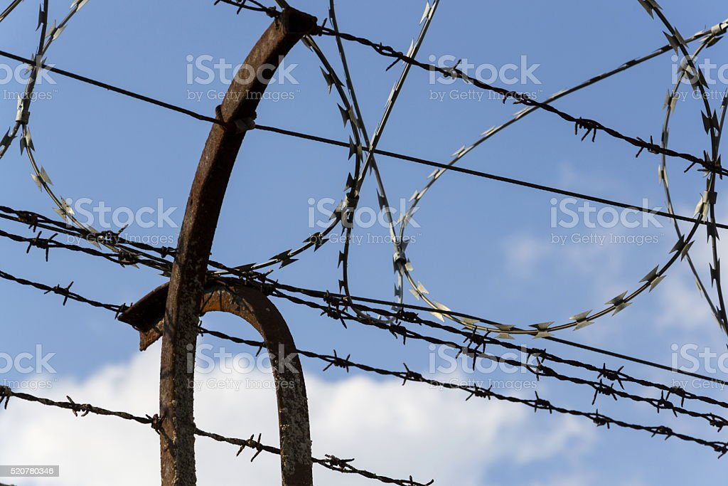 Prison Wall Barbed Wire Fence Detail With Blue Sky Background Stock ...