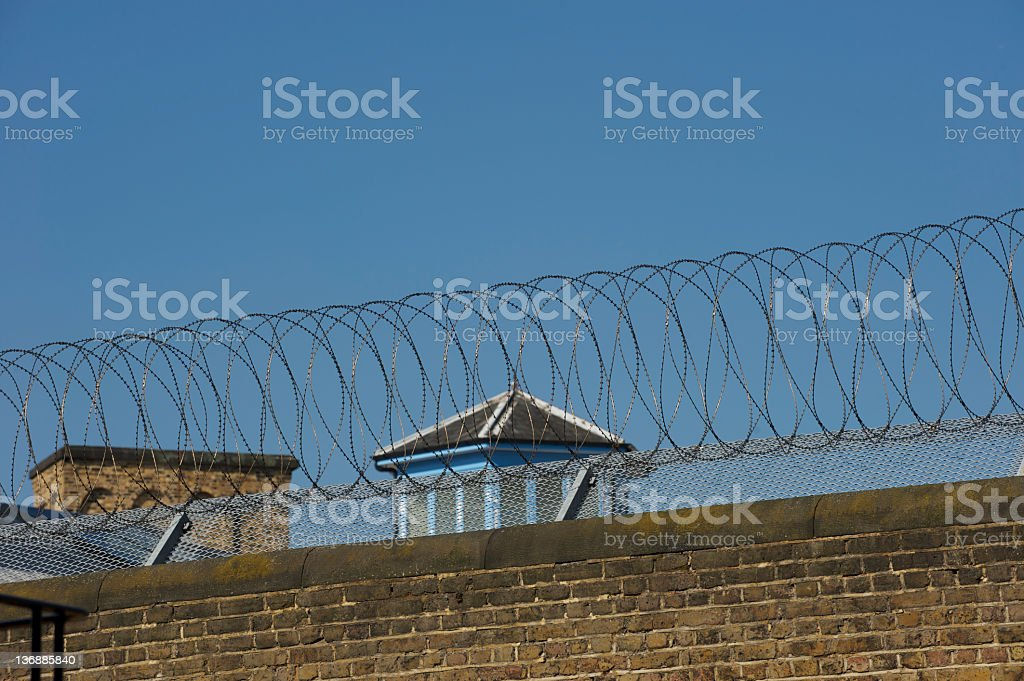 Prison wall topped with razor wire royalty-free stock photo