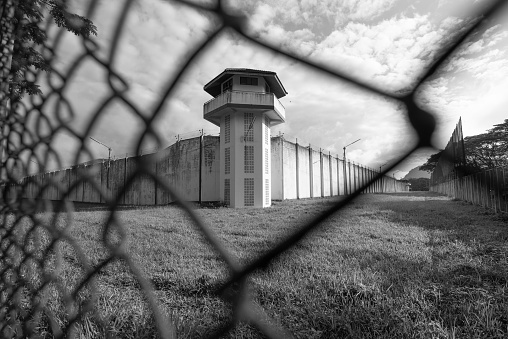 Prison watchtower protected by wire of prison fence.White prison wall and guard tower with coiled barbed wire.Criminal justice imprisonment concept