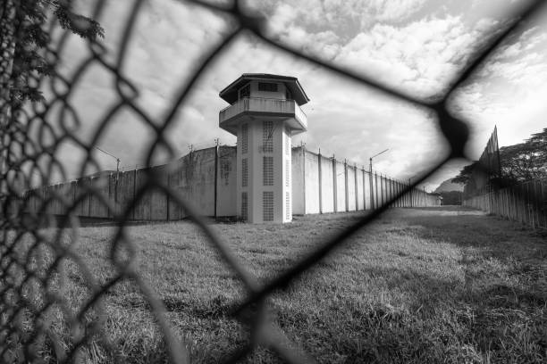 Prison watchtower protected by wire of prison fence.White prison wall and guard tower with coiled barbed wire.Criminal justice imprisonment concept stock photo