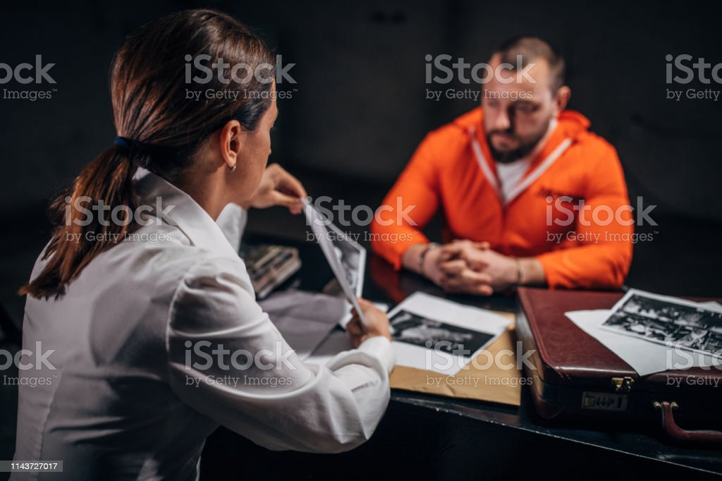 Prisoner and detective Prisoner in orange jumpsuit with handcuffs and female detective sitting in the investigation room Adult Stock Photo