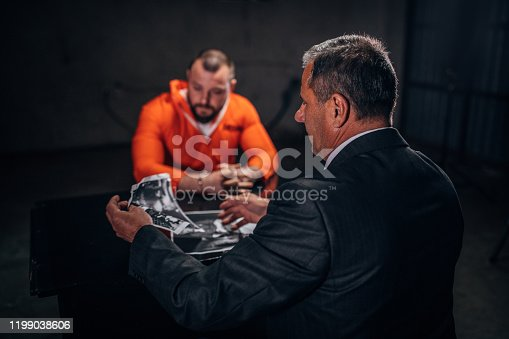 Prisoner in orange jumpsuit with handcuffs and detective sitting in the investigation room