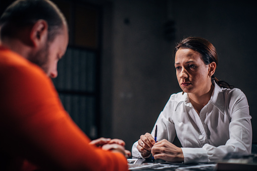 Prisoner in orange jumpsuit with handcuffs and female detective sitting in the investigation room