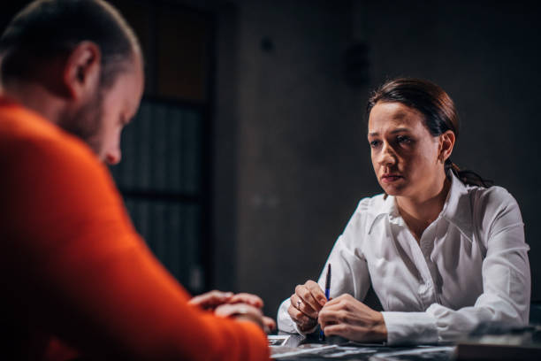 Prisoner and female detective Prisoner in orange jumpsuit with handcuffs and female detective sitting in the investigation room police interview stock pictures, royalty-free photos & images