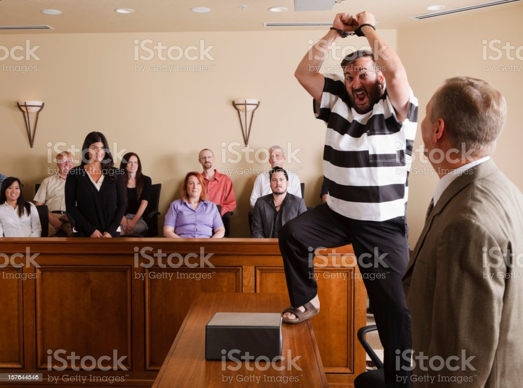 Prisoner Celebrating in Court A man in a prison uniform celebrating his acquittal in court. 40-49 Years Stock Photo