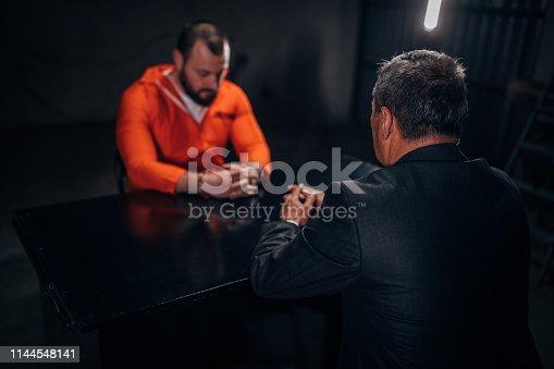 Man detective and man prisoner sitting in dark investigation room.