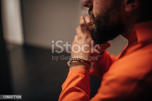 istock Prisoner in orange jumpsuit sitting in prison visiting room 1250077104