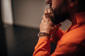One mal prisoner in orange jumpsuit sitting in prison visiting room.