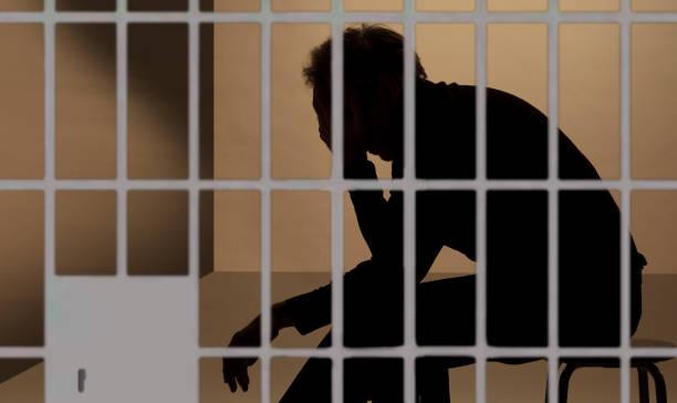 prisonnier en prison, silhouette au-delà des barreaux - prison photos et images de collection