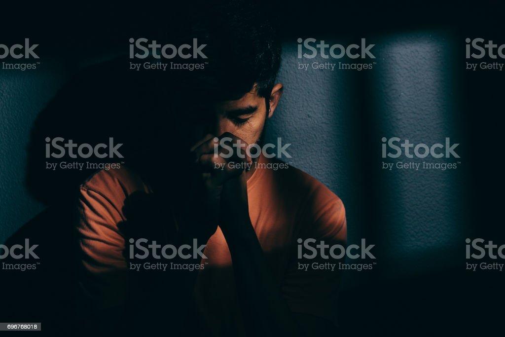 Prisoner man in dark cell depressed or praying stock photo