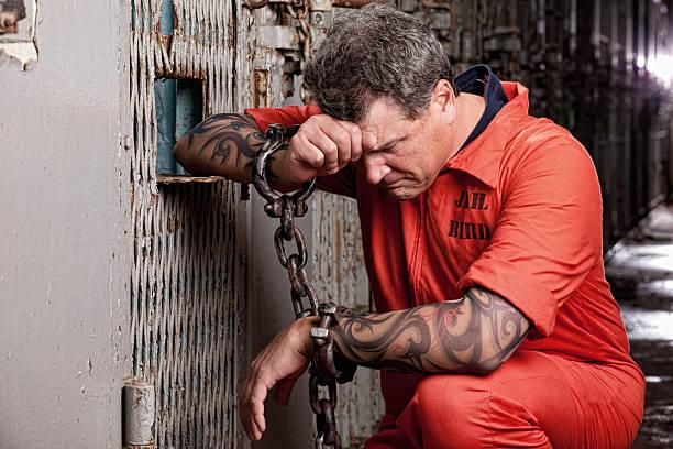Prisoner on His Knees Praying in Jail stock photo