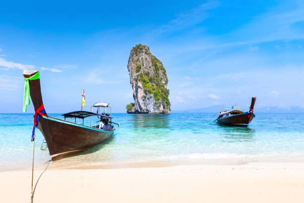 Pristine beach turquoise water longtail boats, Krabi, Thailand travel destination stock photo