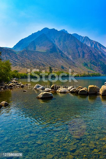 Pristine clear turquoise blue alpine lake with mountain peaks in background