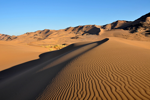 A pristine Namib desert dune in the foreground with a rocky outcrop in the background