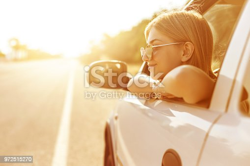 812419994istockphoto Pritty girl traveling in car 972515270