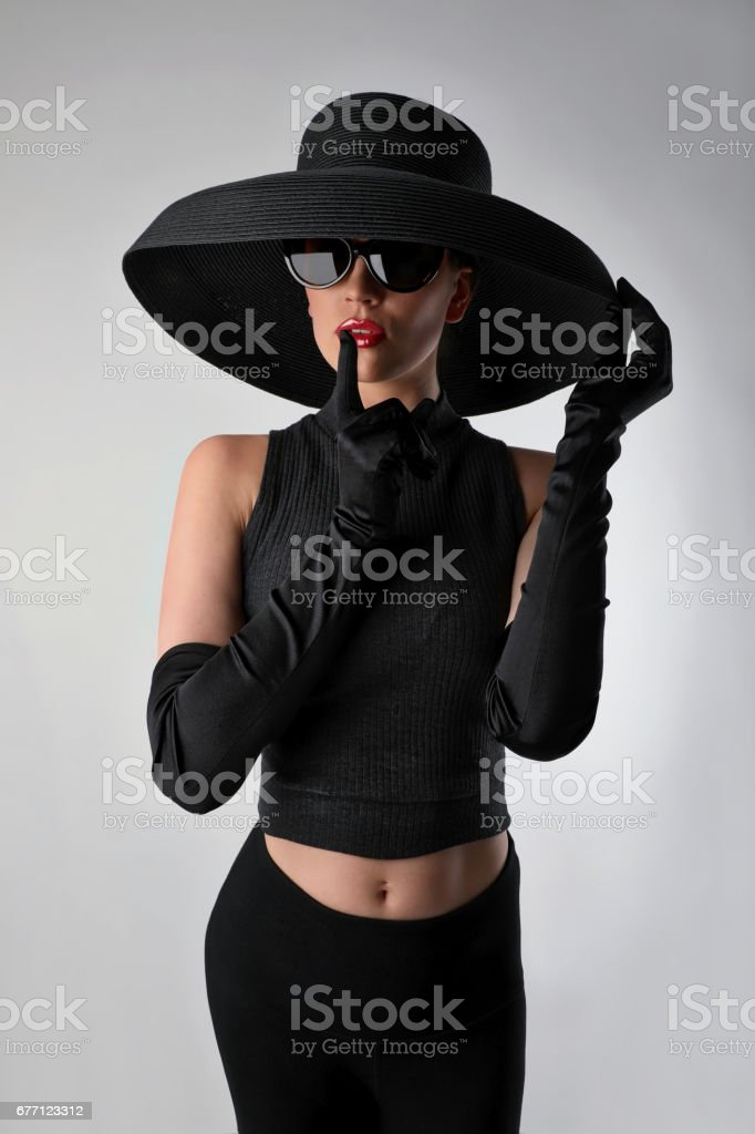 Privacy Concept. Glamorous woman with finger on lips stock photo