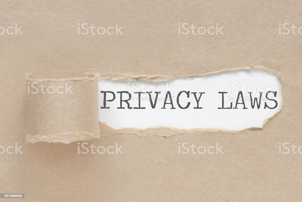 Torn paper revealing the words privacy laws