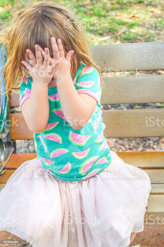Little girl covers her face with her hands sitting on a bench outside