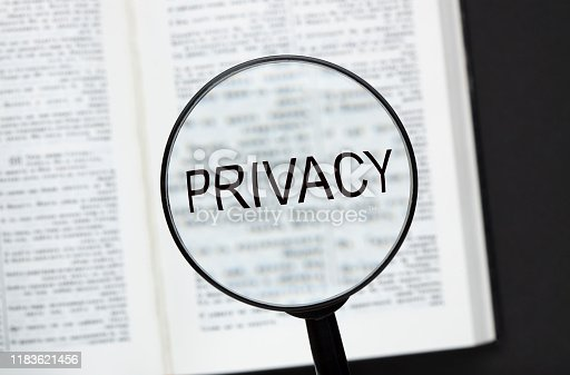 Word Privacy with magnifying glass  over a opened book on black background