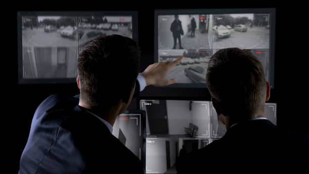 Private agents monitoring CCTV footage, searching for criminal, discussion Private agents monitoring CCTV footage, searching for criminal, discussion security staff stock pictures, royalty-free photos & images