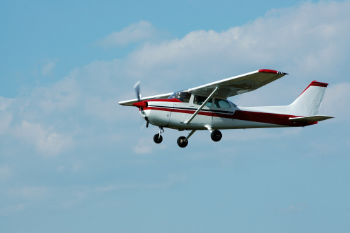 private airplane Cessna 172 in blue sky with white clouds