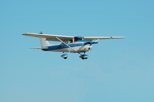 Private four passenger airplane flying on a clear, bright day. Cessna 172.