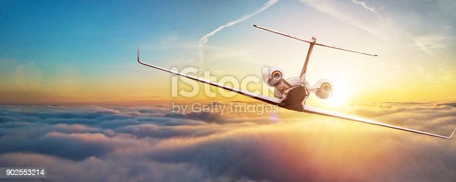 Private airplane jetliner flying above clouds in beautiful sunset light. Travel and business concept. Backside view