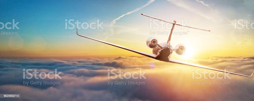 Private airplane jetliner flying above clouds in beautiful sunset light. stock photo