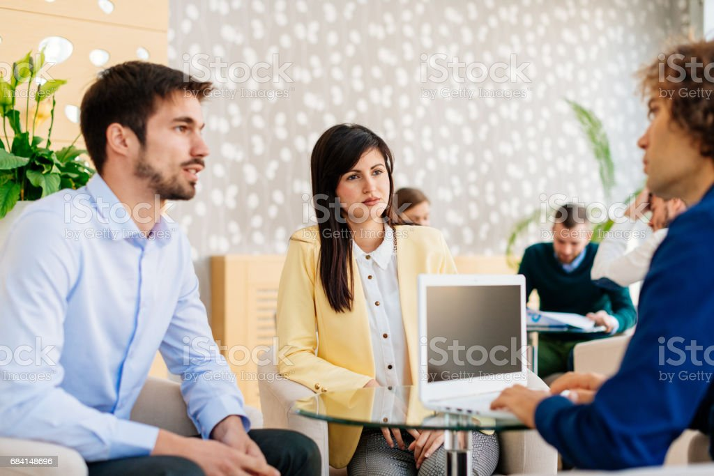 Private banker giving advice to young couple royalty-free stock photo