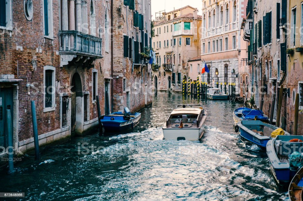 Private boat on a narrow canal in Venice, Italy. stock photo