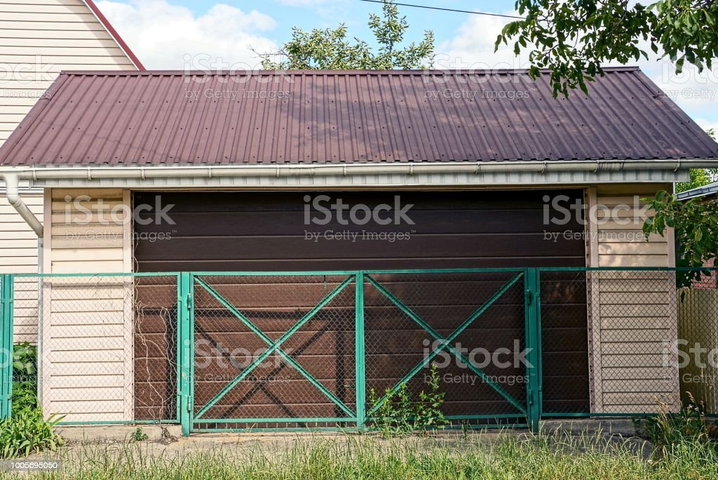 private brown garage behind a green iron fence stock photo