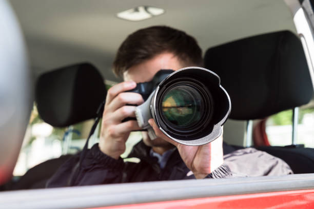 Private Detective Photographing With Slr Camera Side View Of A Private Detective Sitting Inside Car Photographing With Slr Camera detective stock pictures, royalty-free photos & images