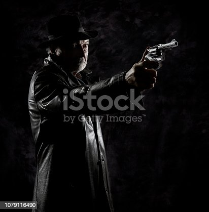 istock A private detective with a revolver in front of a black backdrop. 1079116490