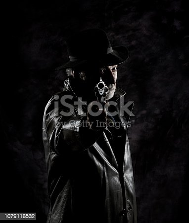 istock A private detective with a revolver in front of a black backdrop. 1079116532