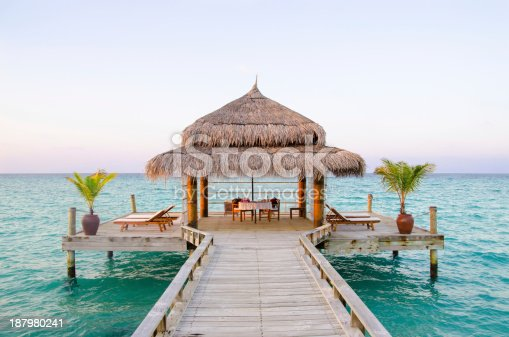 Romantic private dining area on a wooden platform connected to the island with a walkway.