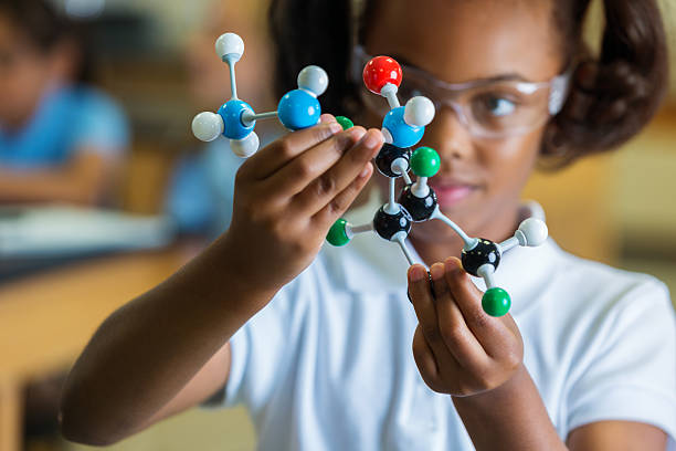 Private elementary school girl examines molecular structure - foto de stock