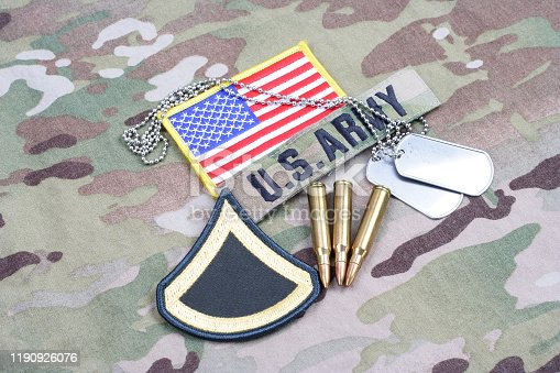 istock US ARMY Private First Class rank patch, flag patch, with dog tag and 5.56 mm rounds on camouflage uniform 1190926076