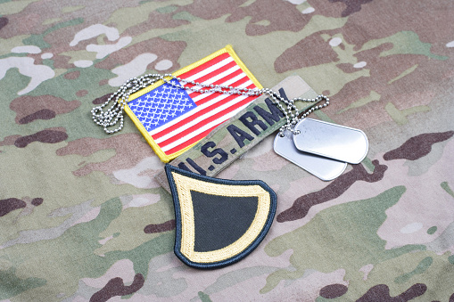 istock US ARMY Private First Class rank patch, flag patch, with dog tag on camouflage uniform 1190926089