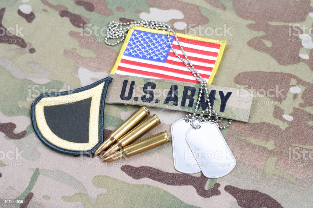 US ARMY Private First Class rank patch, flag patch, with dog tag with 5.56 mm rounds on camouflage uniform stock photo