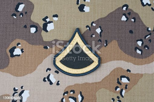 istock US ARMY Private First Class rank patch on desert camouflage uniform background 1206926350