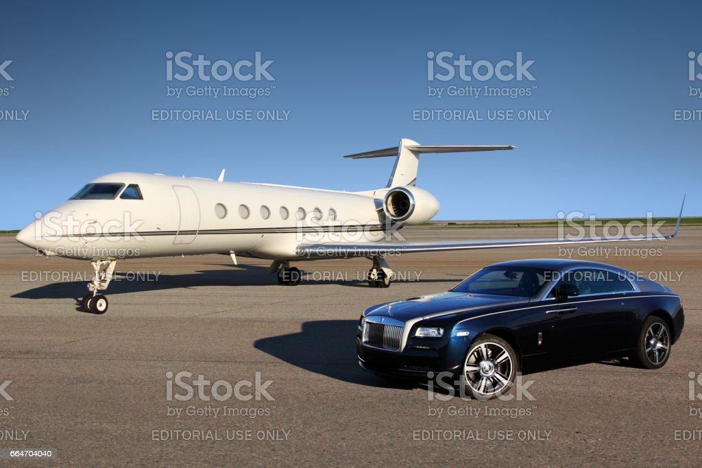 Private Gulfstream G550 executive airplane with Rolls Royce Wraith luxury car shown together at Sheremetyevo international airport. stock photo
