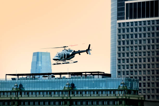 private helicopter flying around buildings stock photo
