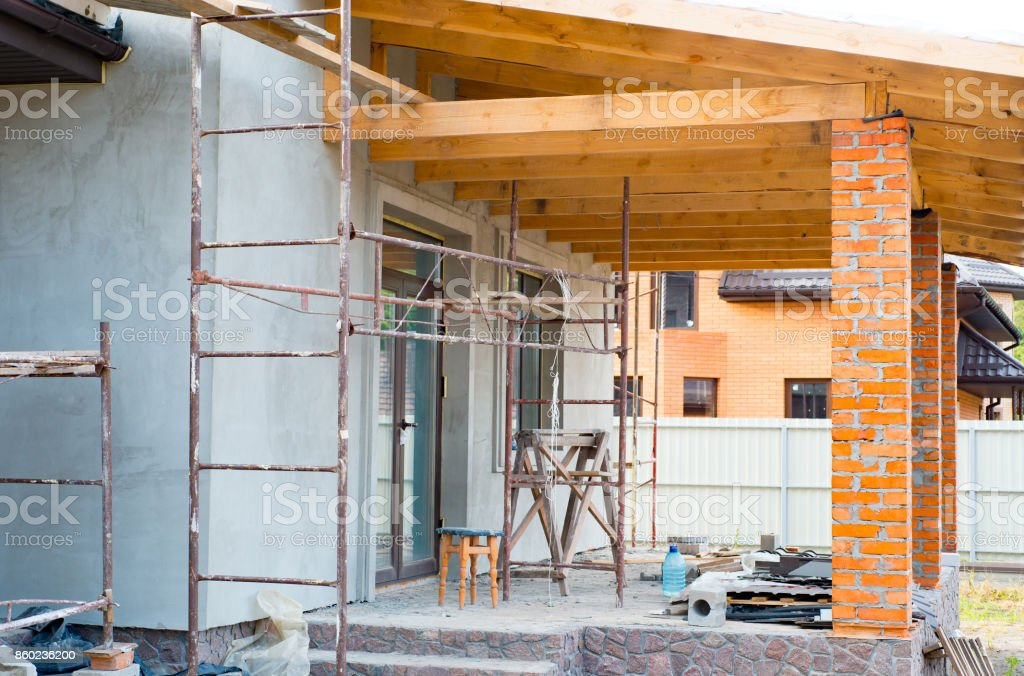 A private house is being constructed, Building a private house with red brick columns, Wooden beams for construction the roof stock photo