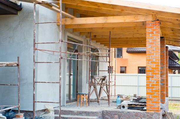 Een privé-woning wordt gebouwd, bouwen van een privé-huis met rode baksteen kolommen, houten balken voor de constructie van het dak foto