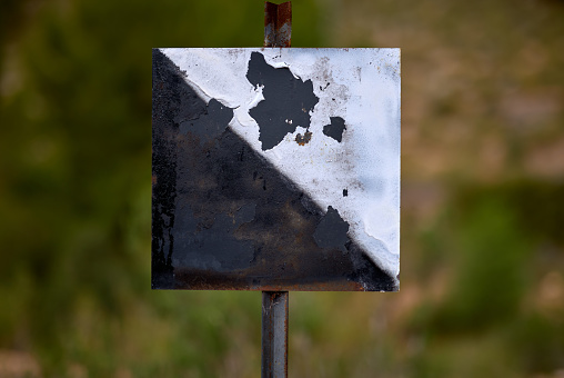detail of a private hunting ground sign with a square shape and a black and white triangle.