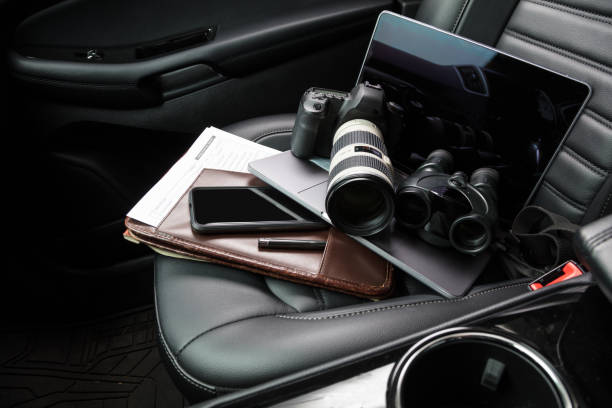 Private investigator tools on car seat Tools for private investigation including camera, smartphone, laptop and binoculars detective stock pictures, royalty-free photos & images