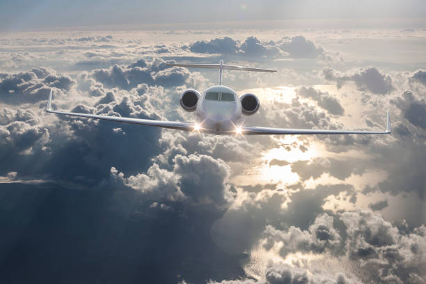Private Jet Flying over clouds stock photo