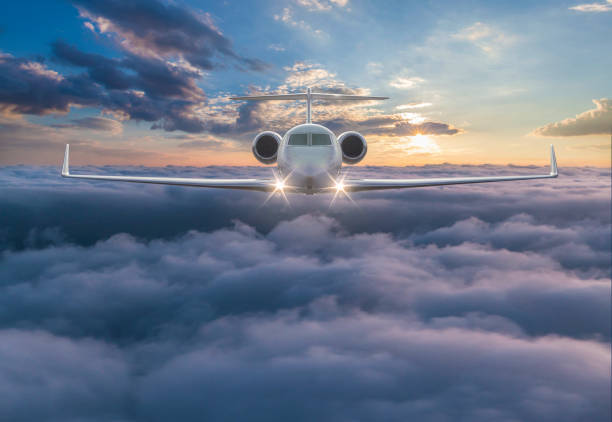 Private jet flying over the clouds stock photo