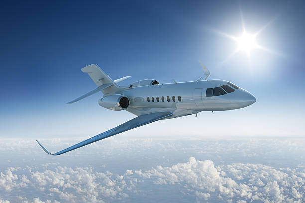 Private jet flying past sun in blue sky stock photo