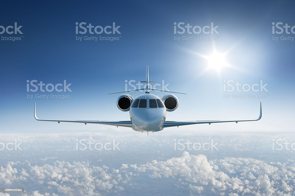 Private jet flying towards the camera in blue sky stock photo